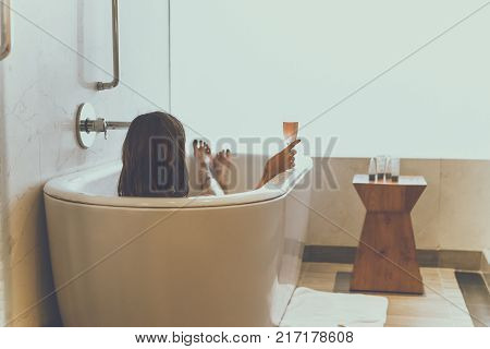 Young attractive woman with champagne glass relaxing in bath. Sexy woman in the bathroom.