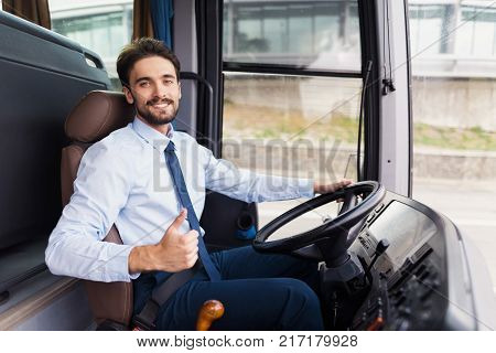 The driver of the tourist bus is smiling and looking at the camera. He is posing behind the wheel of a bus in the driver's seat. The man runs a new black tourist bus.