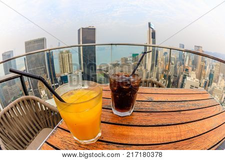 Hong Kong, China - January 1, 2016: coke and juice drinks with city skyline view from the rooftop of The Hennessy in Wan Chai. fisheye angle view.