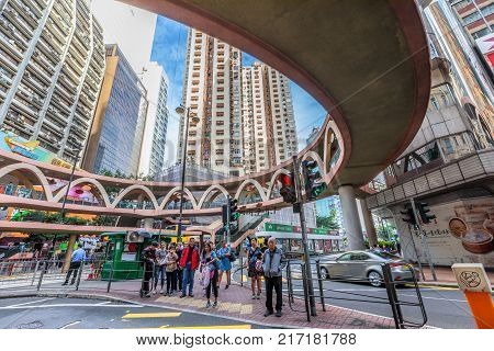 Hong Kong, China - December 6, 2016: people standing at the traffic lights under elevated skywalk between Pennington Street and Yee Wo Street in the famous luxury shopping district of Causeway Bay.