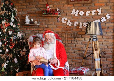 Inquisitive female child listens attentively to interesting story from book read by Santa Claus in cozy and spacious room decorated for New Years holidays with large floor lamp, walls on which Christmas posters hang,