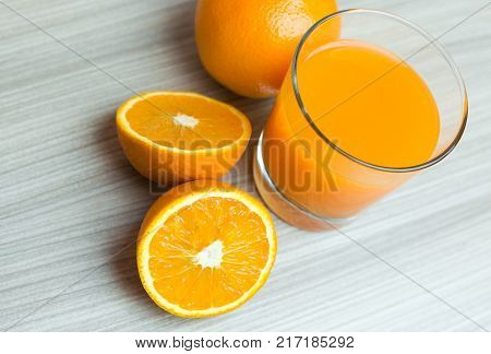 Glass Of Squeezed Orange Juice. Fresh And Juicy Oranges On The Wooden Table.