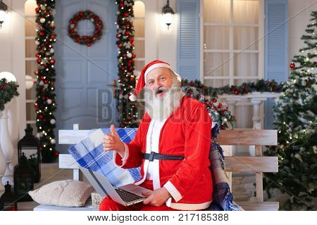 Happy Father Christmas using approving gestures and enjoying with laptop. Cozy room with embellished conifer and twinkling garlands. Concept of cheerful Santa Claus with thumbs up and snug apartments.