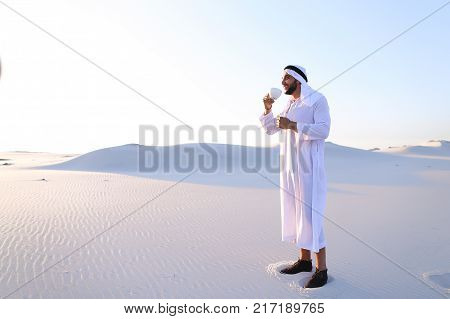 Portrait  confident and happy male Muslim who drinks invigorating coffee drink from white cup and enjoys calm morning, standing in midst of endless sandy desert with pure white sand in open air on warm summer morning. Swarthy Muslim with short dark hair