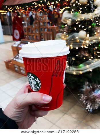 Cup with coffee from Starbucks on the background of a Christmas tree - December 2017