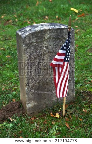 Weathered headstone of a veteran with the American flag in front of the stone.  Green grass surrounds the stone and flag.  Headstone is unreadable, could represent all those lost in battle throughout history.
