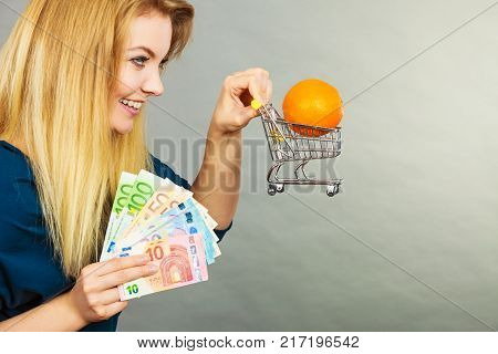 Woman Holding Shopping Cart With Orange Inside