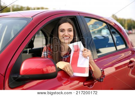 Happy young woman holding learner driver sign in car