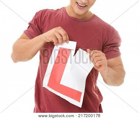 Young man tearing learner driver sign on white background