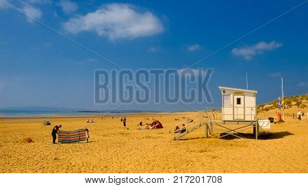 Lifeguard house and holiday makers on Camber Sands Beach, East Sussex England, April 2017