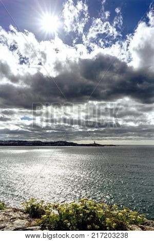 View of the entrance of the bay of La Coruna with the silhouette of the City of La Coruna Galicia. Dramatic sky with dark clouds and sun facing