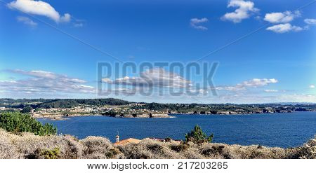 Panoramic view of the cliffs on the coast of La Coruna Bay (Galicia) on the Spanish Atlantic coast. Blue sky with some clouds and calm sea