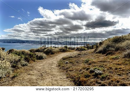 Road on the cliffs on the coast of La Coruna Bay (Galicia) on the Spanish Atlantic coast with the city of La Coruna in the background. Blue sky with some clouds and calm sea