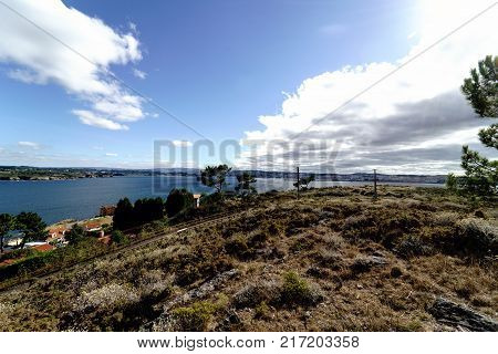 Panoramic view of the coast of La Coruna Bay with a blue sky and clouds receiving the reflection of the sun