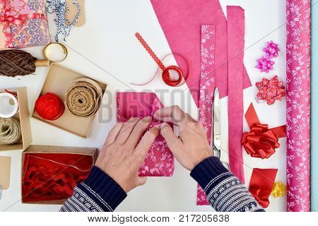high angle shot of a young caucasian man wrapping a gift on a white table full of boxes, wrapping paper with different patterns and strings and ribbons of different colors