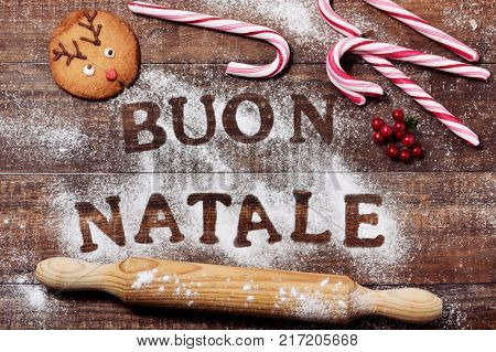 high-angle shot of a wooden table sprinkled with icing sugar or flour where you can read the text buon natale, merry christmas in italian, a rolling pin, some candy canes and a christmas cookie