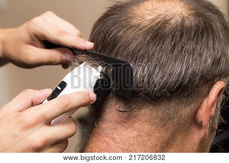 Close up of a male student having a haircut with hair clippers .