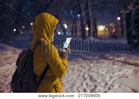young woman standing at night winter city park in the evening and taking picture to share it in social networks