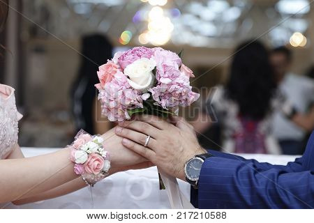 Man putting engagement ring on fiancee finger, young couple is getting engaged, engagement ring on woman hand, ring on finger hand bride
