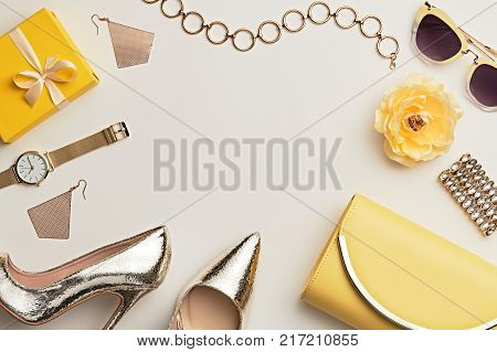 Fashion. Woman Accessories Set. Trendy Gold Heels, Watch, Summer Sunglasses, Glamour fashion Yellow Clutch. Flower. Flat lay. Luxury Stylish Spring lady