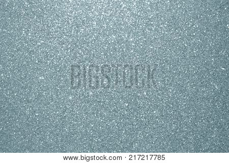 Abstract silver glitter texture background. Glittering silver grain or shining particles with sparkling light effect background for Christmas modern trendy design template