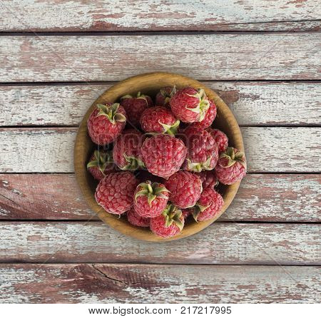 Raspberry top view. Sweet raspberries on a wooden background. Raspberry in a wooden bowl with copy space for text.