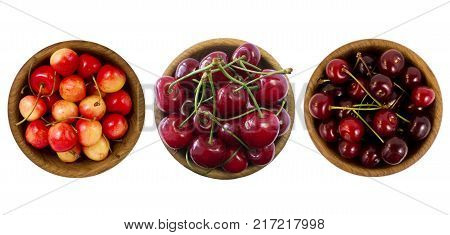 Set of cherries. Sweet cherry mix. Sweet cherry berries in wooden bowl isolated on white background cutout. Cherry fruit with copy space for text. Cherry on white. Red yellow and burgundy cherry