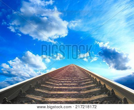 landscape with rails going away to the blue cloudy sky. Cloudy landscape