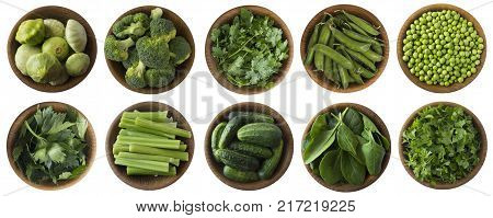 Green vegetables and herbs isolated on a white background. Squash brocoli green peas cucumbers and leaves parsley celery cilantro spinach in wooden bowl with copy space for text. Top view.