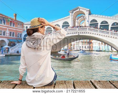 Woman traveler in hat enjoying summer time, Rialto Bridge on the background, Venice, Italy