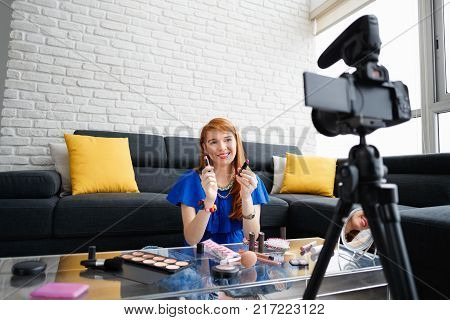 Happy girl at home talking about makeup in front of camera. People and technology, young woman at work as vlogger. Web influencer recording message for internet social networks poster