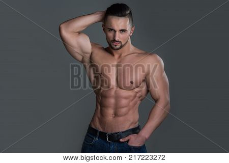 Coach sportsman with bare chest in jeans. Man with muscular body and torso. Sport and workout. Athletic bodybuilder man on grey background. Dieting and fitness.