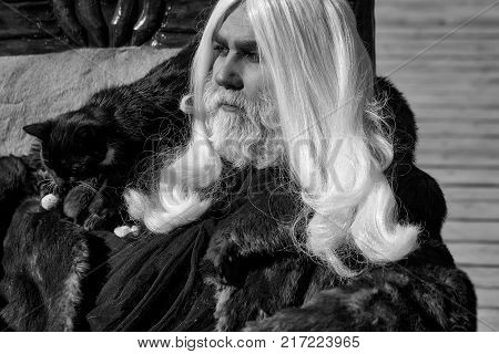 Druid old man with long silver hair beard with black cat on shoulder in fur coat on grey background