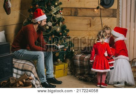 Santa claus kid and bearded man at Christmas tree. Winter holiday and vacation. New year small girl and man fairytale. Xmas celebration fathers day. Christmas happy children and father read book.