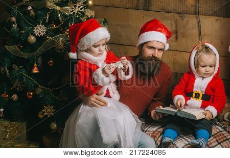 New year small girl and man fairytale. Xmas celebration fathers day. Santa claus kid and bearded man at Christmas tree. Christmas happy children and father read book. Winter holiday and vacation.