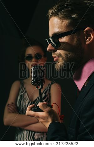 Music and love. Couple in love in glasses sing in microphone. Beauty and vintage fashion music band. Pinup girl and man sing karaoke radio. Singer man and woman with retro hair and makeup. poster