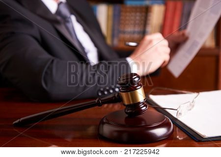 Attorney working, holding Law document with judge's gavel at desk in courtroom lawyer office, tribunal and justice concept