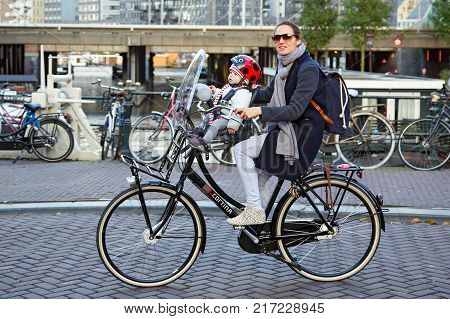 AMSTERDAM/ NETHERLANDS - OCTOBER 22, 2014. A  fashionably dressed woman on a bicycle with a windscreen, carrying her baby in a child seat. Eenhoornsluis bridge over the Princengrach canal. Amsterdam, the Netherlands.