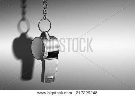 Hanging silver metal whistle close up photo.