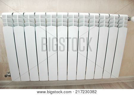 White heating battery in the room close up.