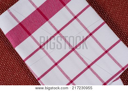 Background for product. Checked tablecloth in a red and white cage on textured surface, view from above.