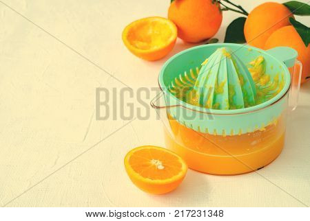 Freshly squeezed orange juice in turquoise juicer on white background, horizontal, copy space, toned