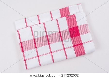 Background for product. Checked tablecloth in a red and white cage on white surface, view from above.