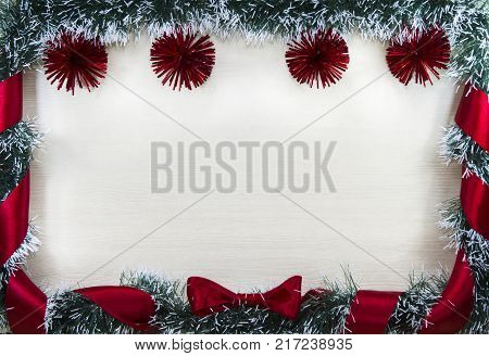 Christmas design-Christmas card bordered by pine and red balls and ribbon with bow place for text. Studio photography.