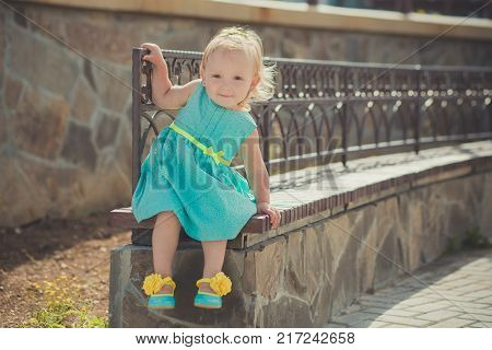 Cute little baby girl enjoying summer time in central park sights wearing colourful dress and sandals with blond hairs and pink cheeks.
