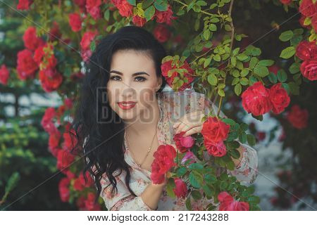 Amazing mystic lady woman with black dark curly hairs pink cheeks pout deep red lips wearing designer couturier shirt and blue short jeans shorts with brown belt posing sit for bush of flowers roses.