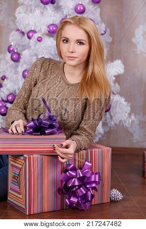 Amazing beautiful face lady girl with perfect skin and blond hairs posing for christmas holidays close to new year white pine tree and presents in studio.