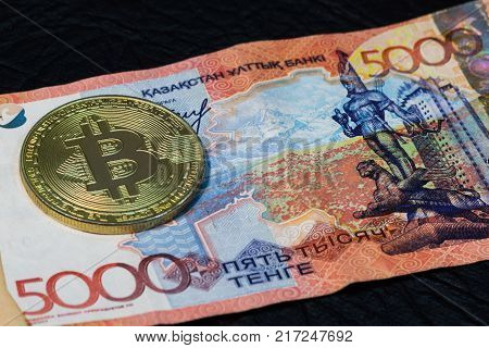 The gold bitcoin coin lies on the background of Five thousand KZ tenge.