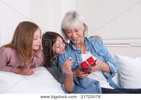 Girls offering present to grandmother poster