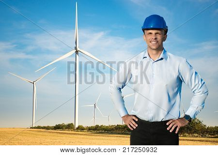 Young blue collar worker or engineer wearing in yellow helmet stands in the field with wide smile against wind turbines farm. Half-length portrait.